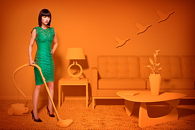 Caucasian woman in orange old-fashioned livingroom vacuuming carpet - p555m1304580 by Chris Clor