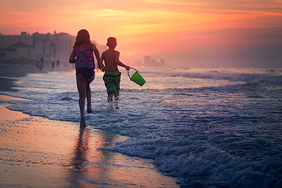 Siblings paddling in sea at sunset, North Myrtle Beach, South Carolina, United States - p924m1506711 by Rebecca Nelson