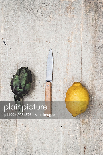 High angle close up of fresh lemon, artichoke and kitchen knife on grey background. - p1100m2084876 by Mint Images