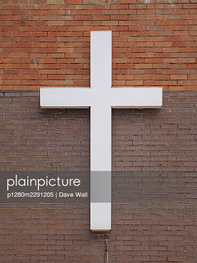 Oversized white cross placed on brick wall - p1280m2291205 by Dave Wall