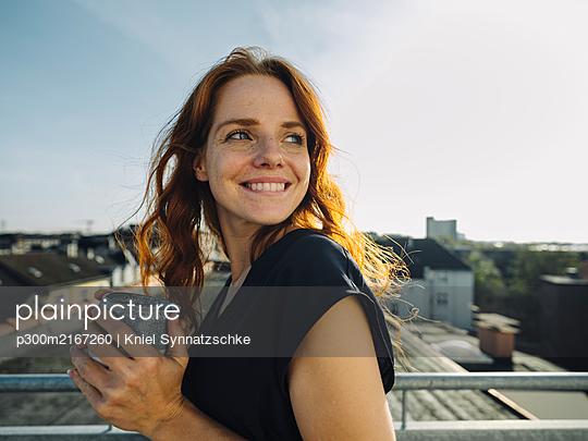 Smiling redheaded woman having a coffee break on rooftop terrace - p300m2167260 by Kniel Synnatzschke