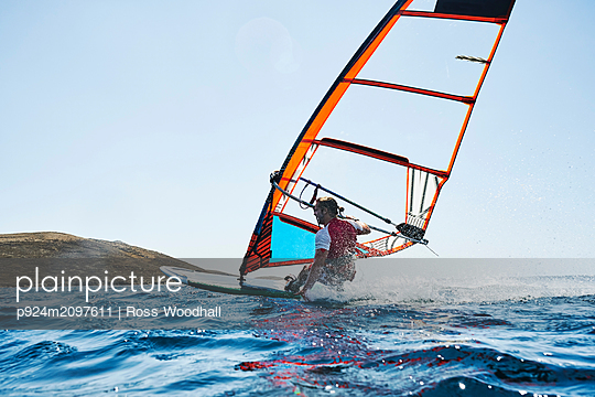Young man leaning back windsurfing ocean waves, surface level rear view, Limnos, Khios, Greece - p924m2097611 by Ross Woodhall