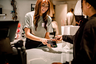 Female customer paying through smart phone to smiling saleswoman at store - p426m2213171 by Maskot