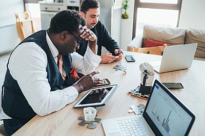 Businessmen using smartphone in loft office - p429m2091246 by Eugenio Marongiu