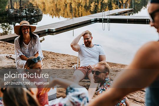 Happy friends sitting at lake - p312m2217266 by Plattform