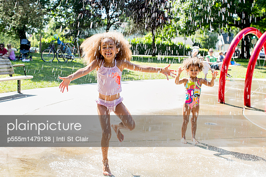 Mixed race girls playing in fountain - p555m1479138 by Inti St Clair