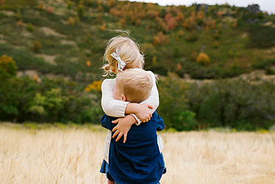 Girl hugging her brother - p1427m2038241 by Jessica Peterson