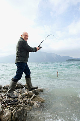 Germany, Bavaria, Walchensee, Senior man fishing in lake - p3007282f by Westend61