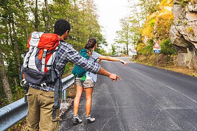 Italy, Massa, couple hitchhiking on a road in the Alpi Apuane mountains - p300m2062911 von William Perugini