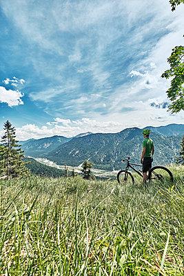 Germany, Bavaria, Isar Valley, Karwendel Mountains, mountainbiker on a trip having a break on alpine meadow - p300m2104609 by Wilfried Feder