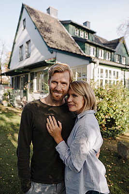 Portrait of smiling couple standing in front of their home - p300m2166633 by Kniel Synnatzschke