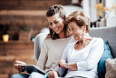 Happy grandmother and woman looking at digital tablet while sitting on sofa at home - p300m2274956 by Gustafsson