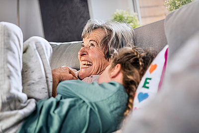 Cheerful grandmother lying by granddaughter on sofa at home - p300m2287223 by Stefanie Aumiller