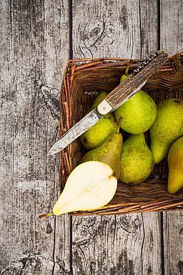 Wickerbasket with pears and pocket knife on grey wood - p300m977981f by Larissa Veronesi