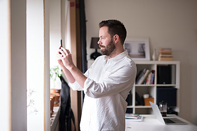 Man photographing with cell phone - p312m2052440 by Viktor Holm