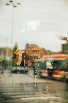 Smiling businessman wearing headphones while using mobile phone seen through glass window at office - p426m2159321 by Maskot