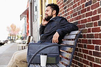 Hispanic man sitting on city bench using cell phone - p555m1305253 by Roberto Westbrook