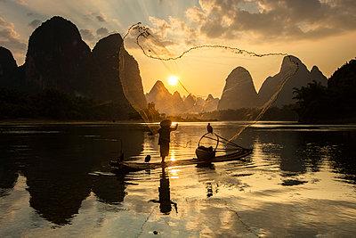 Cormorant fisherman throwing net on Li River at dawn, Xingping, Yangshuo, Guangxi, China - p651m2271088 by Jeremy Flint photography