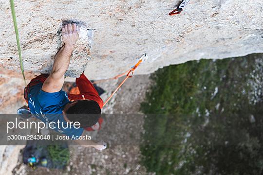 Courageous male athlete climbing mountain - p300m2243048 by Josu Acosta