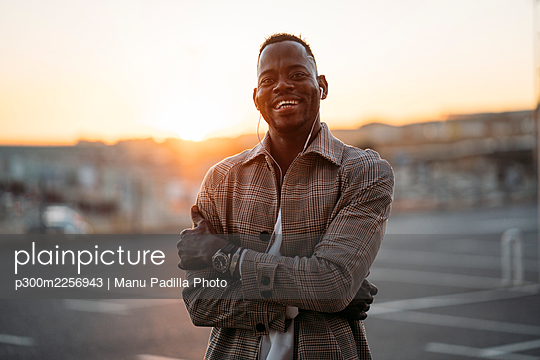 Cheerful man with arms crossed standing at parking lot during sunset - p300m2256943 by Manu Padilla Photo