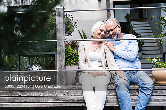 Man smiling while sitting by woman at balcony - p300m2294184 by Uwe Umstätter