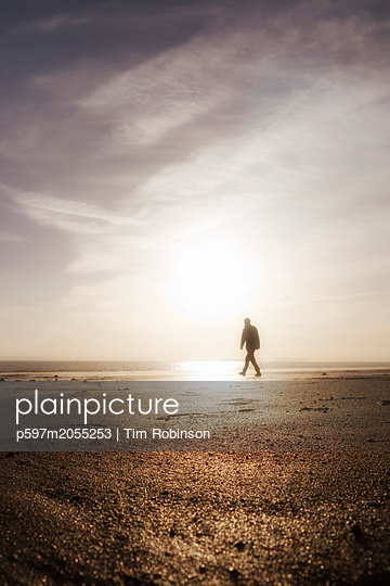 Silhouette man walking on beach with low sun - p597m2055253 by Tim Robinson