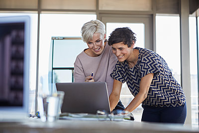Two smiling businesswomen sharing laptop at desk in office - p300m2081096 by Rainer Berg