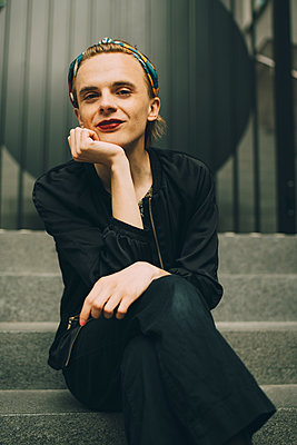 Portrait of smiling young man sitting on staircase - p426m2169410 by Maskot