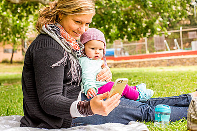 Caucasian mother and baby daughter using cell phone in park - p555m1412119 by Adam Hester