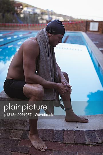 Male swimmer sitting on the starting block near swimming pool - p1315m2091057 by Wavebreak
