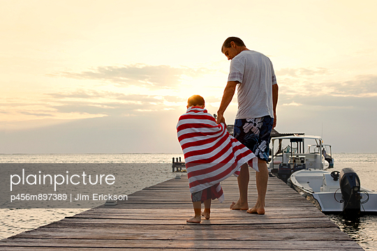 Father and son walking hand in hand toward a boat. - p456m897389 by Jim Erickson
