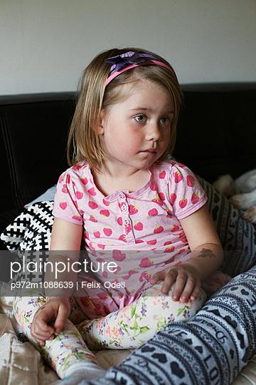 Mädchen sitzt auf einem Sofa - p972m1088639 von Felix Odell