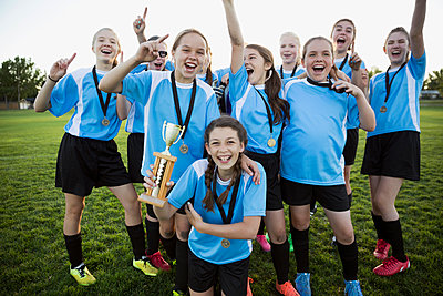 Portrait exuberant middle school girl soccer team celebrating and cheering with trophy - p1192m1173911 by Hero Images
