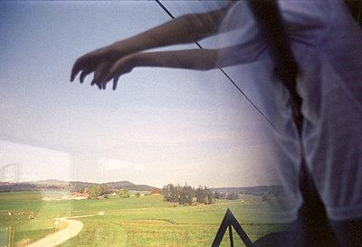 Nicht erkennbarer Mensch greift nach Landschaft, halb gespiegelt in Zugfenster, Allgäu, Bayern, Deutschland - p1316m1160360 von Peter von Felbert