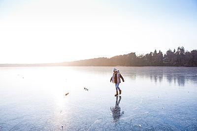 Germany, Brandenburg, Lake Straussee, girl walking on frozen lake - p300m1581007 by Julia Otto