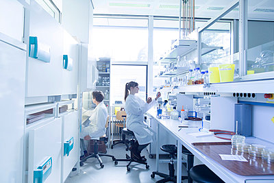 Two female natural scientists working at microbiology laboratory - p300m979150f by Sigrid Gombert