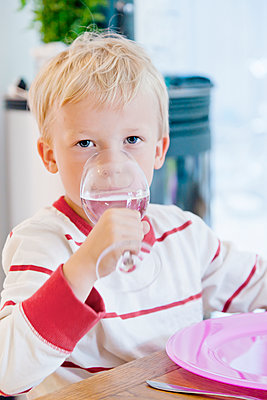 Little blonde boy drinking water from wine glass in kitchen - p312m1551946 by Johner Images