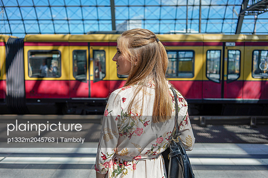 A female waiting for a train in a train station - p1332m2045763 by Tamboly