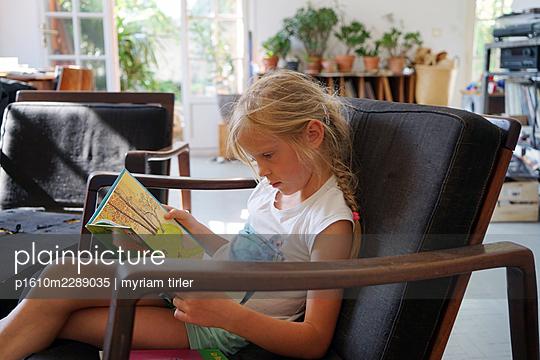A little girl reading a book - p1610m2289035 by myriam tirler