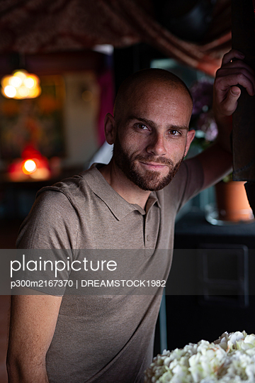 Portrait of smiling man in a bar - p300m2167370 by DREAMSTOCK1982