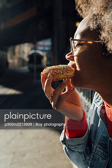 Close-up of young woman wearing eyeglasses eating donut on sunny day - p300m2213908 by Boy photography