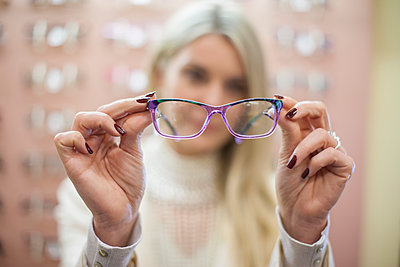 Blond woman selecting new glasses in opticians shop - p300m1189620 by zerocreatives