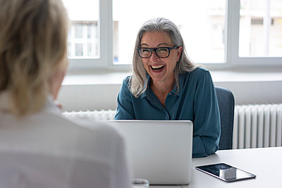 Laughing mature businesswoman talking to young businesswoman at desk in office - p300m2155611 by Robijn Page