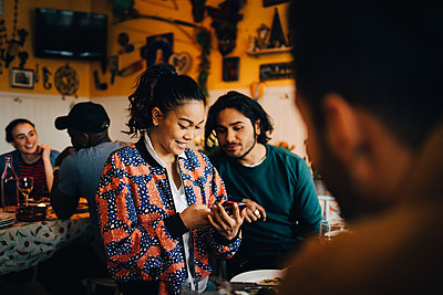 Smiling young woman sharing smart phone with male friend while sitting at restaurant during dinner party - p426m2046310 by Maskot