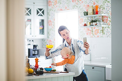 Multi-tasking mother food blogging while carrying daughter in kitchen at home - p426m2116963 by Maskot