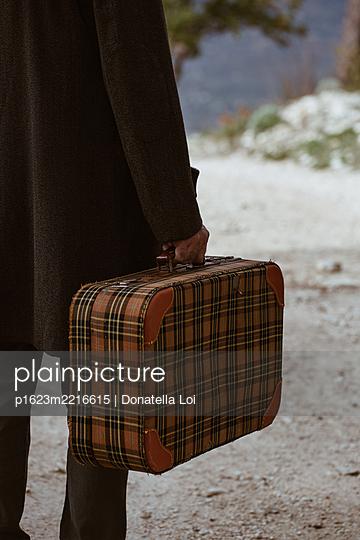 Man with vintage suitcase - p1623m2216615 by Donatella Loi