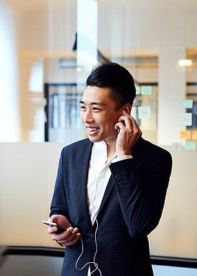 Asiatischer Mann telefoniert mit Headset - p1124m1181492 von Willing-Holtz