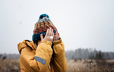 young boy with covering his face with his hands whilst playing in snow - p1166m2157409 by Cavan Images