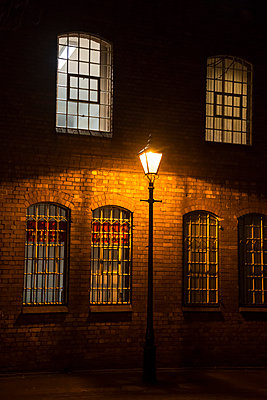 Single street lamp and barred windows at night - p1170m1516284 by Bjanka Kadic