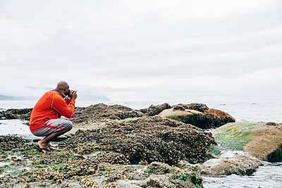 Black man photographing on beach - p555m1311459 by Inti St Clair